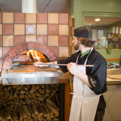Chef placing a pizza in the wood-fired oven at the Hearth & Vine Cafe.