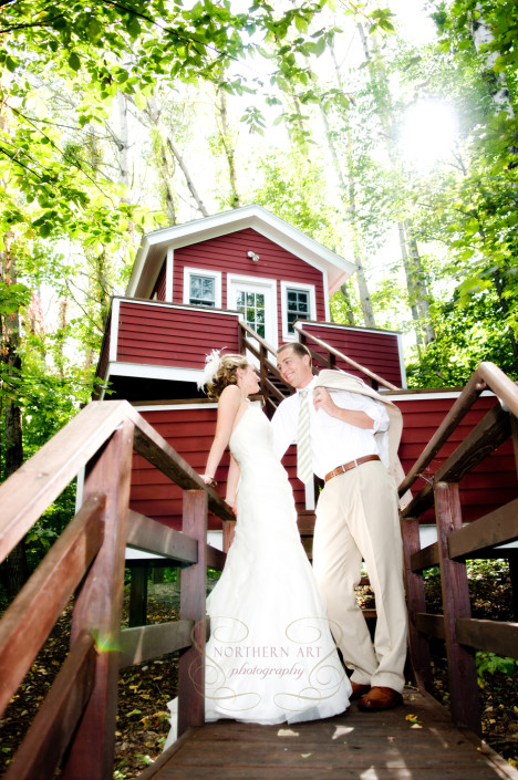 Bride and groom standing at the stairs of the tree house.