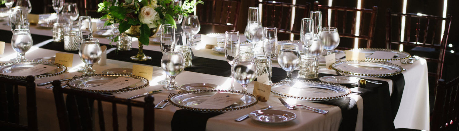 Close up of a wedding reception table with dramatic lighting in the Pegasus Barn.