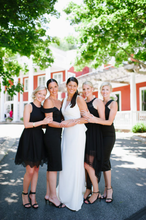 A bride and her bridesmaids in the drive in front of the Inn at Black Star Farms.