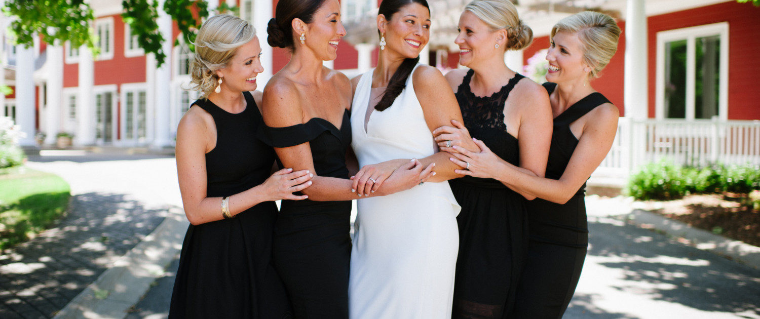 A bride and her four bridesmaids in front of the Inn at Black Star Farms.