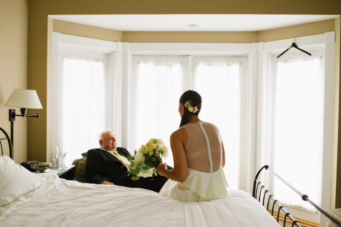 Bride talking with the father of the bride in a guest room at the Inn at Black Star Farms.