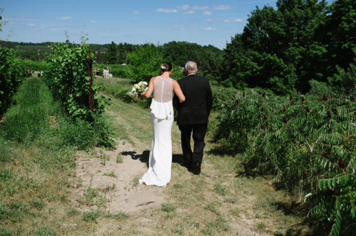 Father of the bride walking the bride through the vineyard at Black Star Farms Suttons Bay.