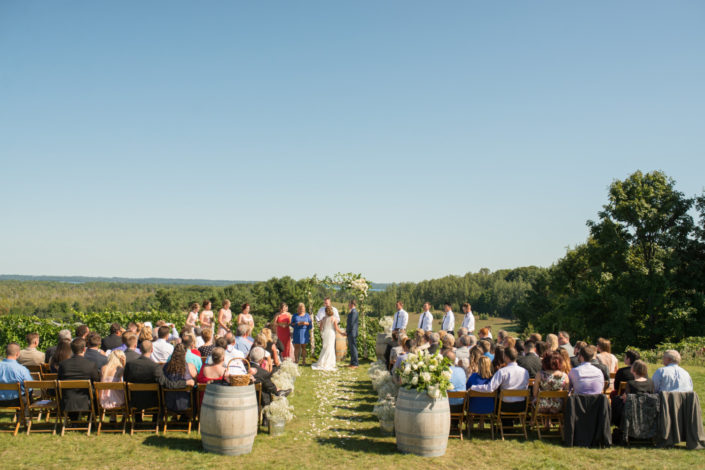 Wedding ceremony with bride and groom and guests at the scenic hilltop vineyard.