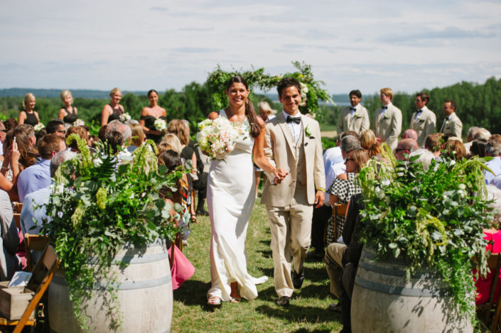 Bride and groom walking up the aisle at a summer wedding in our scenic hilltop vineyard.