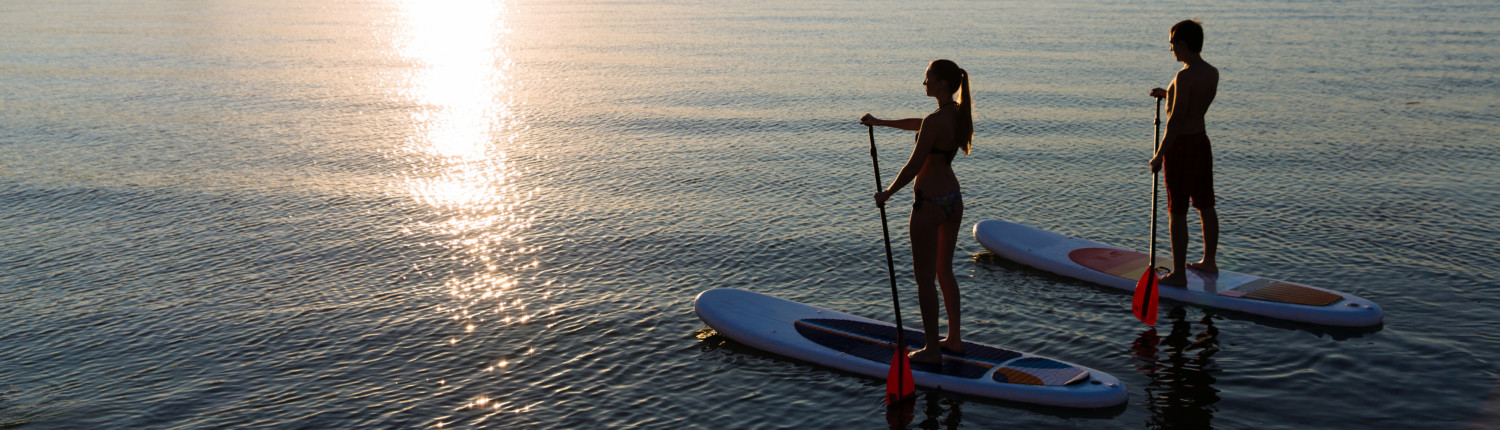 Couple using stand-up paddle boards as part of the Outdoor Adventure Package at the Inn at Black Star Farms.