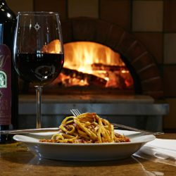 Image of pasta and a glass of red wine in front of the wood-fired oven at the Hearth & Vine Cafe