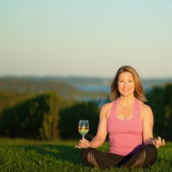 Yoga instructor with a glass of wine in a vineyard.