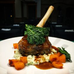 Roasted lamb chop entree with mashed potatoes, and carrots.