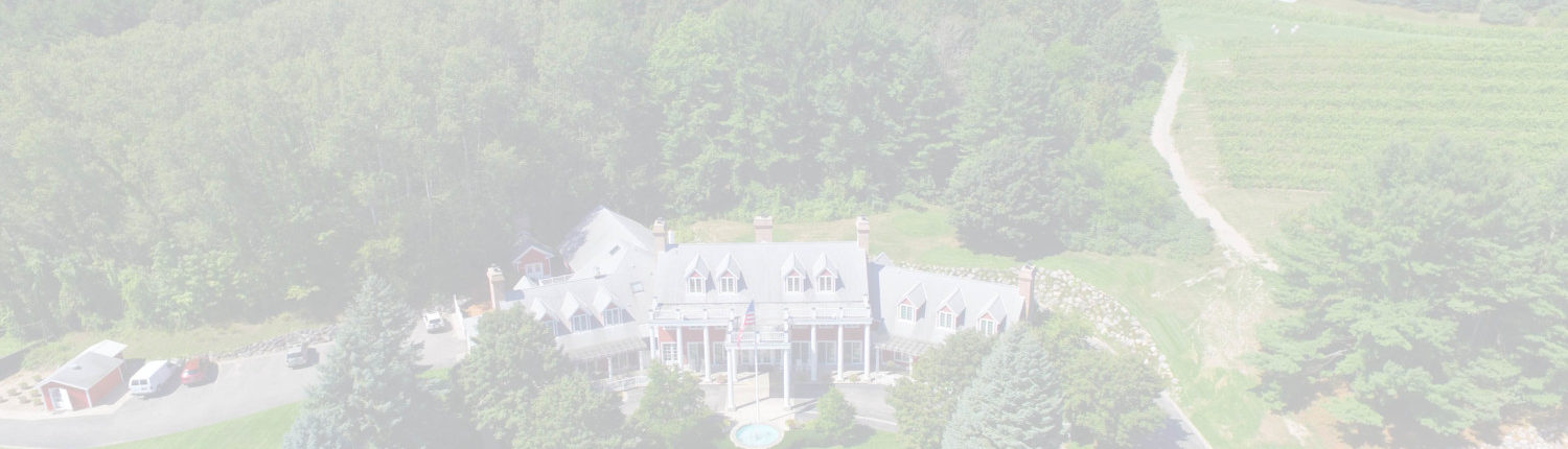 Aerial view of the Inn at Black Star Farms with surrounding forest and vineyards.