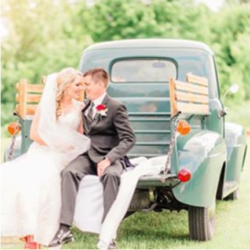 Wedding couple sitting in the back of a vintage pickup truck.