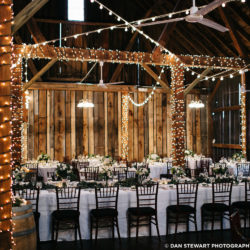 Beautiful wedding reception tables in the Pegasus Barn with lights wrapped around the beams.