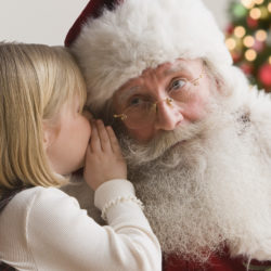 Girl whispering into Santa's ear.