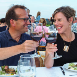 Couple toasting red wine at the Arcturos Dining Series in the vineyard.