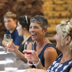 People having fun wine tasting in our Barrel Room at Black Star Farms Suttons Bay.