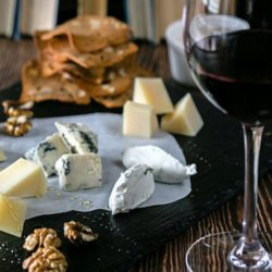 Cheese board with crackers and a glass of red wine.