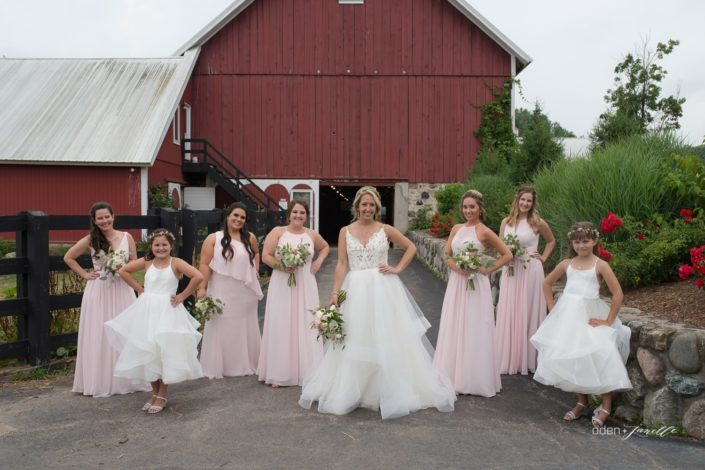 A bridal party standing in front of the barns at the stables at Black Star Farms.