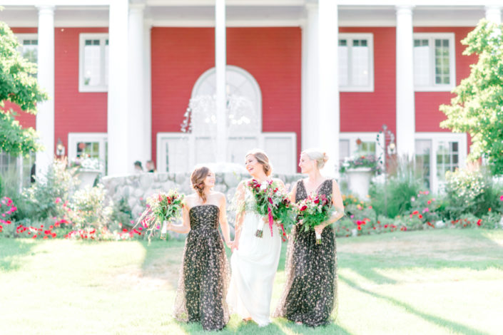 A bride and her two bridesmaids in front of the fountain an the Inn at Black Star Farms.