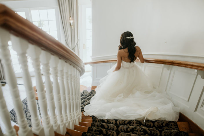 Bride descending the spiral staircase in the front foyer of the Inn at Black Star Farms.