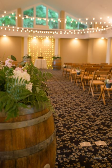 Wedding ceremony set up with chairs, alter, wine barrels, flowers, and lights.