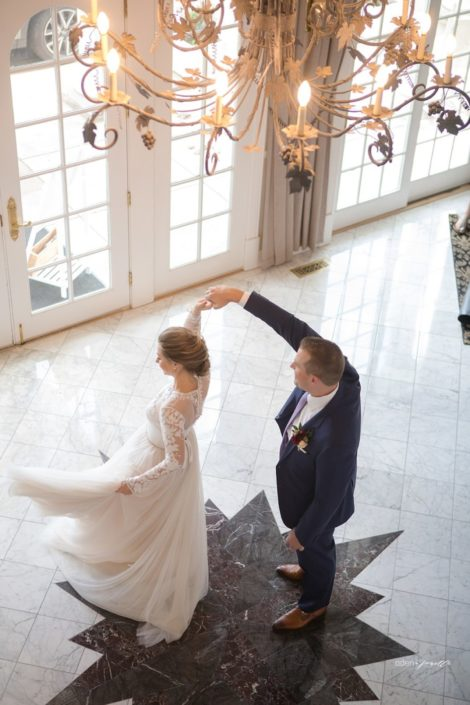 Groom spinning his bride on the star in the foyer.