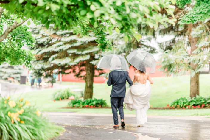 Bride and groom walking in the rain with umbrellas.