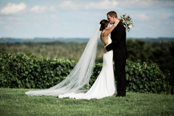 Bride with long veil and groom embracing in front of grape vines.