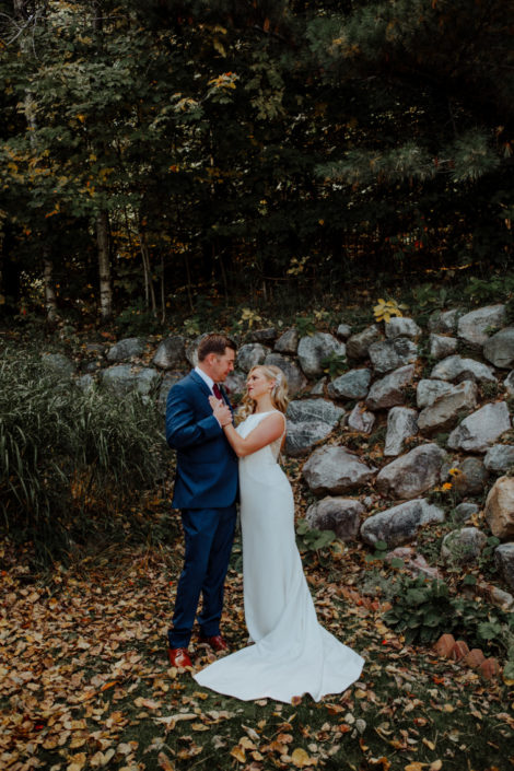 Bride and groom standing among fall leaves in front of the rock wall.