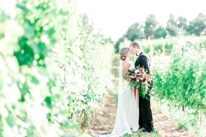 Wedding couple between the vines at Black Star Farms Suttons Bay.