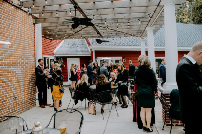 Guests enjoying a small wedding reception on the covered patio at the Inn at Black Star Farms.