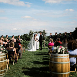 Wedding ceremony with guests at our scenic hilltop vineyard site.
