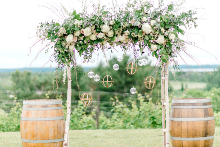Wedding alter with flowers and wine barrels in the vineyard.