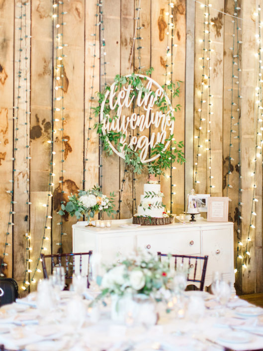 Wedding cake on decorated table with lights behind in the Pegasus Barn.