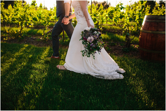 Groom and bride with bouquet walking past grape vines.