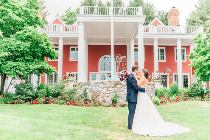 Wedding couple standing in the lawn in front of the Inn at Black Star Farms.