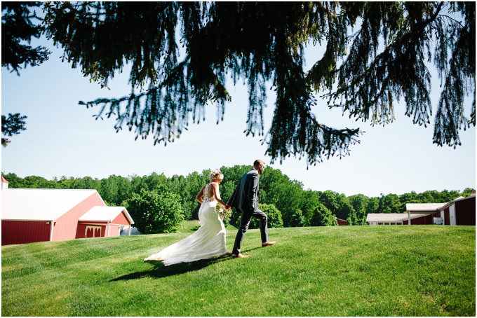 Bride and groom walking on the lawn with a barn in the background.
