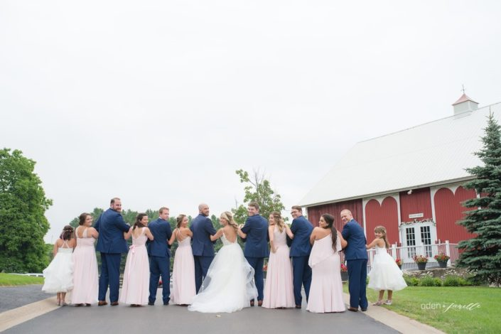 Wedding party walking down the drive and looking back at the camera in front of the Pegasus Barn.