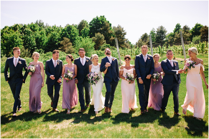 Wedding party standing in a line with the vineyard in the background.