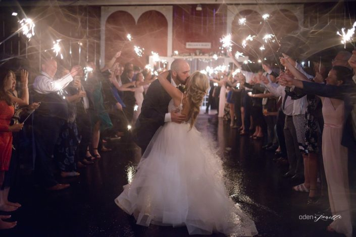 Bride and groom kissing in front of the Pegasus Barn with guests holding lit sparklers.