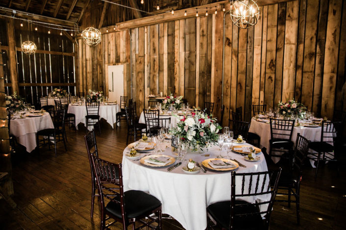 Round tables set for a wedding reception in the Pegasus Barn.