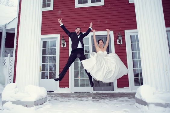 Bride and groom jumping during winter on the front porch of Inn at Black Star Farms.