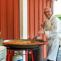 Chef cooking paella in a large paella pan on the patio at the Hearth and Vine Cafe.