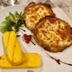 A plate with with polenta and Frico which is a traditional dish consisting of potatoes and cheese from North East Italy.