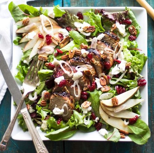 Example of a grilled pork tenderloin salad with dried cherries, nuts and fresh apple slices.