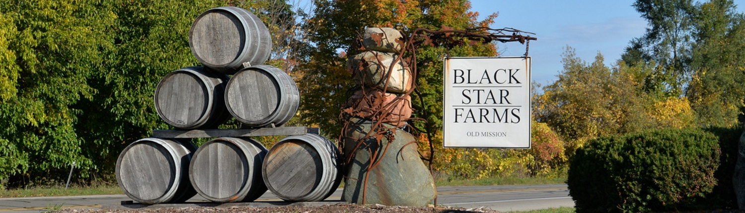 Black Star Farms Old Mission sign with wine barrels.