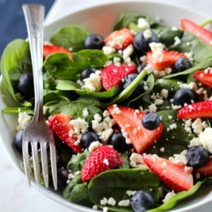 A spinach salad with fresh berries and feta cheese.