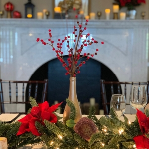 Holiday table with decorated fireplace mantle in the foreground.