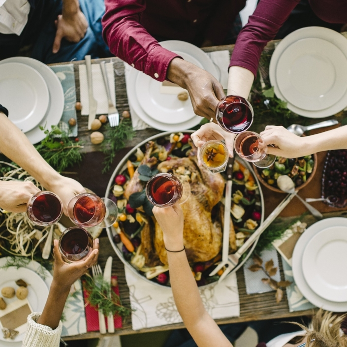People clinking glasses of wine over a Thanksgiving table including a roasted turkey and table decorations.