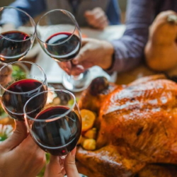 Example of people enjoying red wine with roasted turkey at the dinner table.
