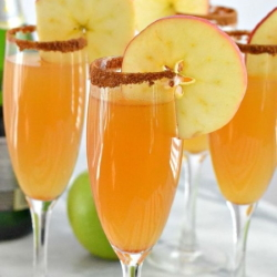 Example of cinnamon rimmed Apple Cider Mimosas with garnished with fresh apple wheel.